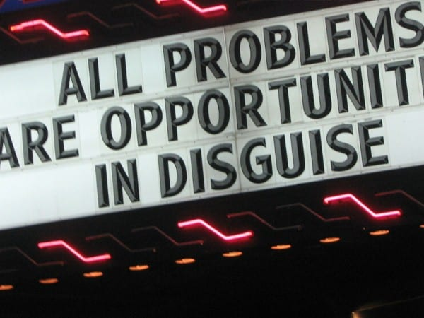 "A theater sign with ""all problems are opportunities in disguise"" text on it"