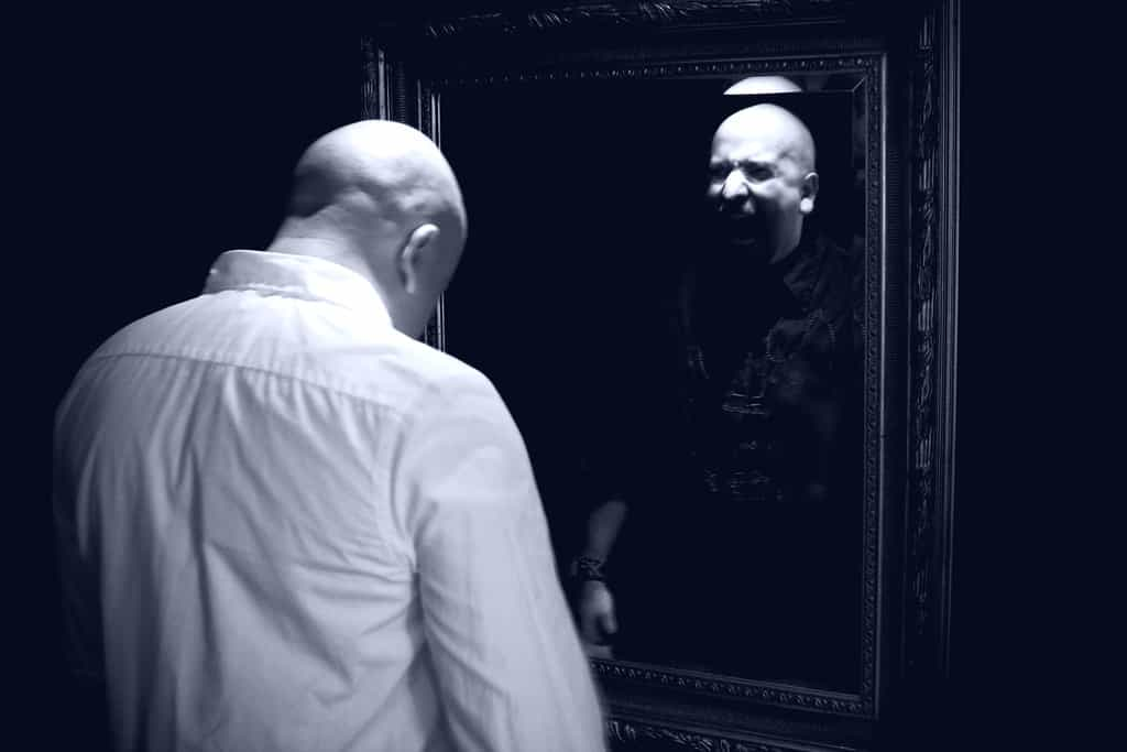 a man looking at his evil twin in a mirror