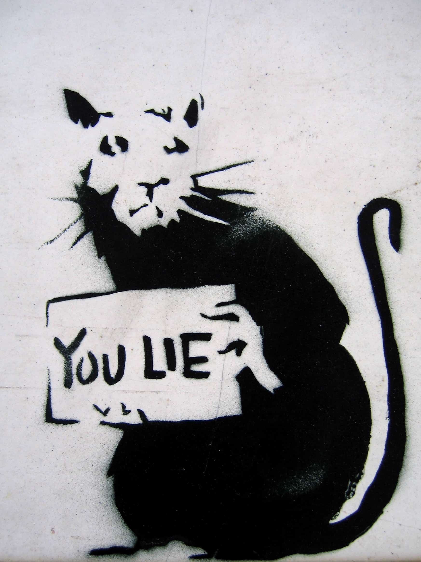 a graffiti of a rat holding a sign written you lie
