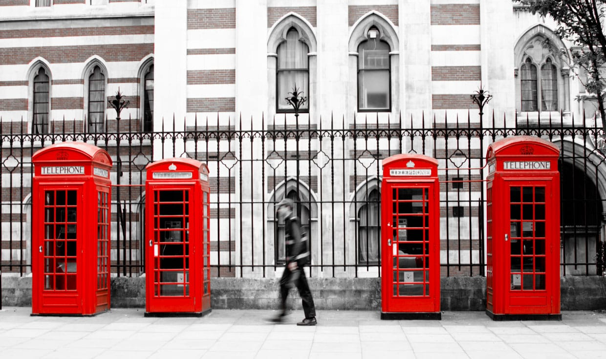 Someone walking in front of multiple red phone booth in London, UK
