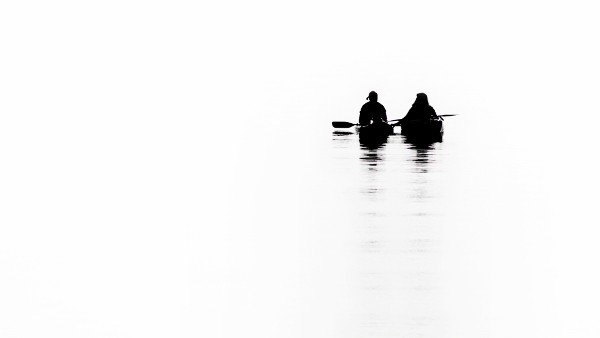 two people canoeing in a white picture